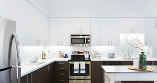 Modern kitchens with designer quartz countertops, stainless steel appliances and European-style wood cabinetry